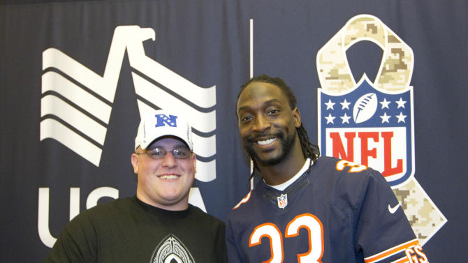 In this photo provided by IMG Consulting, Jonathon Carpenter, left, a member of the Warrior Transition Battalion, and Chicago Bears corner back Charles Tillman (33) pose or a picture at Schofield Barracks Thursday, Jan. 24, 2013, in Honolulu. Members of the Warrior Transition Battalion met with six NFL All-Star Football Players for lunch, autographs and to share their stories on how they were wounded serving their county in war at the USAA NFL sponsored event. (Eugene Tanner/AP Images for USAA. IMG Consulting