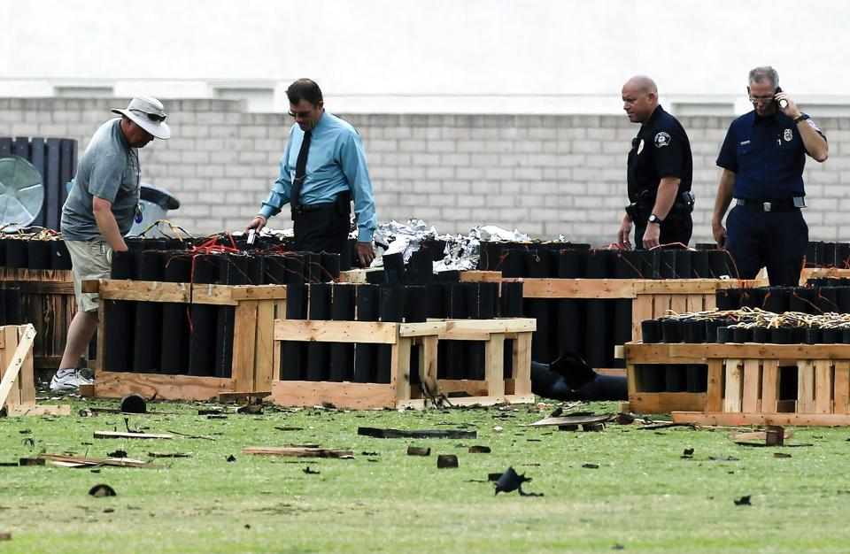 Police officials investigate a site in Simi Valley, Calif., Friday July 5, 2013 where an explosion Thursday injured more than two dozen people at a fireworks display. The explosion occurred when a wood platform holding live fireworks tipped over, sending the pyrotechnics into the crowd of spectators. (AP Photo/Nick Ut)
