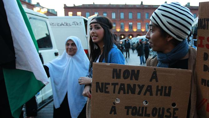 """A French demonstrator holds a placard that reads: """"No Netanyahu in Toulouse"""" as another hold a Palestine flag during a demonstration in Toulouse, southwestern France, Wednesday, Oct. 31, 2012.  Israeli Prime Minister Benjamin Netanyahu is visiting France on Wednesday and Thursday and will pay homage to a rabbi and three Jewish schoolchildren killed by a radical Islamist gunman  in France's worst terrorist attack and worst anti-Semitic attack in years. (AP Photo Bob Edme) French demonstrator hold a placard reads """"No Netanyahu in Toulouse"""" as another holds a flag of Palestine during a demonstration in Toulouse, southwestern France, Wednesday, Oct. 31, 2012. Israeli Prime Minister Benjamin Netanyahu is visiting France on Wednesday and Thursday and will pay homage to a rabbi and three  Jewish schoolchildren killed in France's worst terrorist attack and worst anti-Semitic attack in years. (AP Photo/Bob Edme)"""