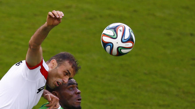 Iran's Jalal Hosseini and Nigeria's Emmanuel Emenike jump for the ball during their 2014 World Cup F soccer match at the Baixada arena in Curitiba