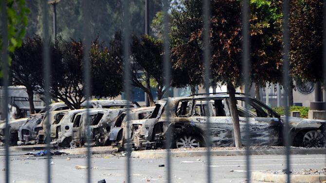 In this photo taken Saturday, Sept. 15, 2012, several dozen burned cars remain in the parking lot of the U.S. Embassy, a day after several thousand demonstrators angry over a film that insults the Prophet Muhammad stormed the compound, Tunis, Tunisia. Leaked conversations in which alcohol bans and the imposition of religious law were mentioned have raised fears Tunisia's new government may not be moderate at all, especially in the context of mob attacks on the U.S. Embassy that coincided with the American ambassador's killing in neighboring Libya. (AP Photo/Hassene Dridi)