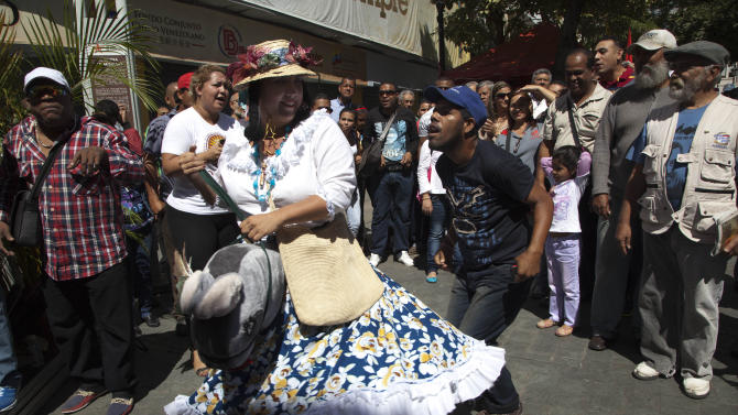 A bystander joins a performer in the traditional folk dance, La Burriquita, in Plaza Bolivar, a popular gathering place for supporters of President Hugo Chavez, in Caracas, Venezuela, Wednesday, Jan. 9, 2013. Venezuela's congress has voted to postpone the inauguration of Chavez, which was scheduled for Thursday, to let him recover from cancer surgery in Cuba. Critics say that violates the country's constitution. On Wednesday, Venezuela's Supreme Court backed the congress, ruling the Jan. 10th inauguration can be postponed. (AP Photo/Ariana Cubillos)