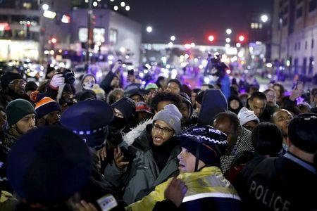 Protesters confront police officers during a demonstration after the release of a video showing the shooting of Laquan McDonald, in Chicago, Illinois