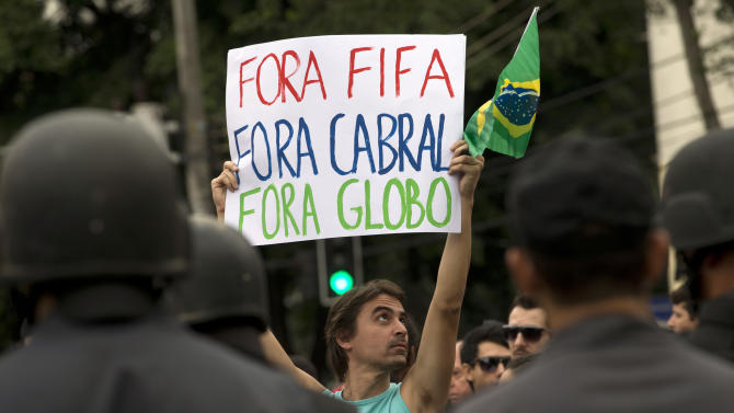 "A man holds a sign that reads ""FIFA out, Cabral out ( Rio de Janeiro Governor, Sergio Cabral), Globo out ( Brazilian news network O Globo )"" as demonstrators march toward the Maracana stadium ahead of the Confederations Cup final in Rio de Janeiro, Brazil, Sunday, June 30, 2013. Protesters have taken to the streets all over Brazil in the past two weeks, calling for a wide-range of reforms. Public approval of Brazilian President Dilma Rousseff's government has suffered a steep drop in the weeks since massive protests broke out across the country, according to Brazil's first nationwide poll released since the unrest began.(AP Photo/Silvia Izquierdo)"