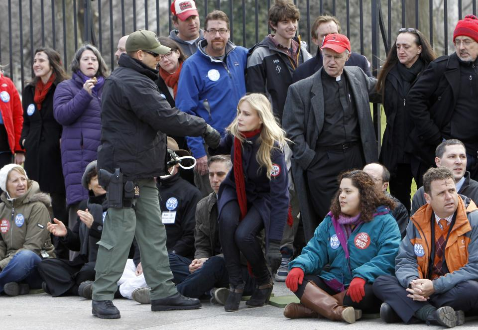 Actress Daryl Hannah is helped up before she is arrested outside the White House in Washington, Wednesday, Feb. 13, 2013, as prominent environmental leaders tied themselves to the White House gate to protest the Keystone XL oil pipeline..  (AP Photo/Ann Heisenfelt)