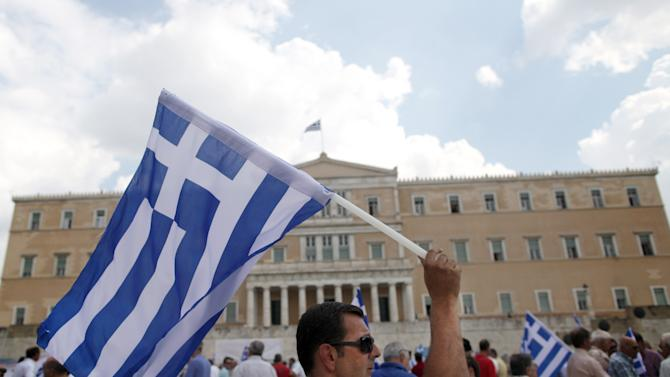A retired military officer carries a Greek flag during a protest against planned austerity measures outside the Greek parliament in Athens, Wednesday, Sept. 19, 2012. Greece's economy will have contracted by 25 percent by the time the recession ends, the finance minister said Tuesday, as the government remained locked in talks with rescue lenders for its next major austerity program. (AP Photo/Petros Giannakouris)