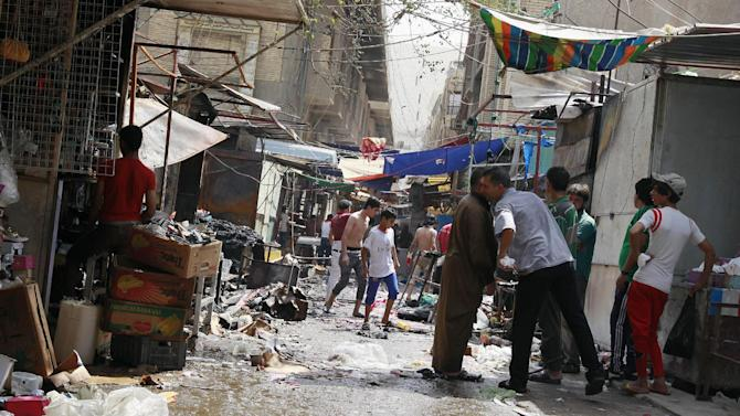 Civilians inspect the site of a bomb attack in Shorja Market in Baghdad, Iraq, Thursday, July 17, 2014. A bomb hidden in a wooden cart exploded near a Shiite mosque in one of Baghdad's largest markets, killing and wounding civilians. (AP Photo/Hadi Mizban)