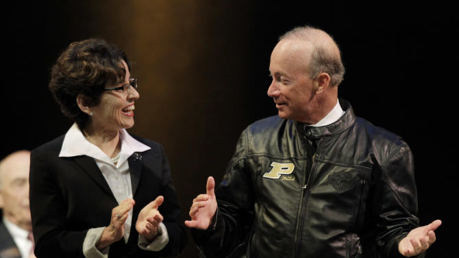 Indiana Gov. Mitch Daniels displays his new Purdue leather jacket given to him by the board of trustee to current Purdue University president France Cordova after he was named as the next president of Purdue University by the school's  trustees in West Lafayette, Ind., Thursday, June 21, 2012. Daniels will take the helm of the school after leaving office in January and succeeds Cordova who will leave in July after five years at Purdue's helm. (AP Photo/Michael Conroy)