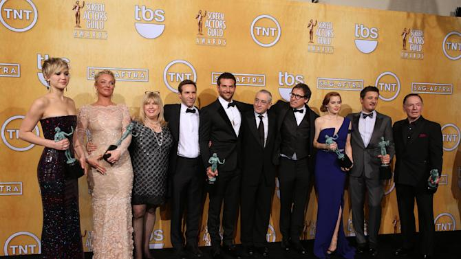 """From left, Jennifer Lawrence, Elisabeth Rohm, Colleen Camp, Alessandro Nivola, Bradley Cooper, Robert De Niro, David O. Russell, Amy Adams, Jeremy Renner and Paul Herman pose in the press room with the award for outstanding performance by a cast in a motion picture for """"American Hustle"""" at the 20th annual Screen Actors Guild Awards at the Shrine Auditorium on Saturday, Jan. 18, 2014, in Los Angeles. (Photo by Matt Sayles/Invision/AP)"""