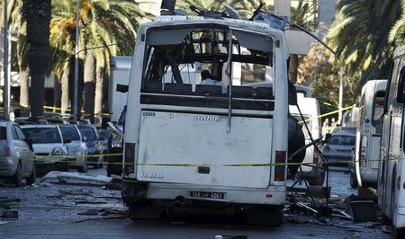 Tunisian forensics police inspect a Tunisian presidential guard bus at the scene of a suicide bomb attack in Tunis