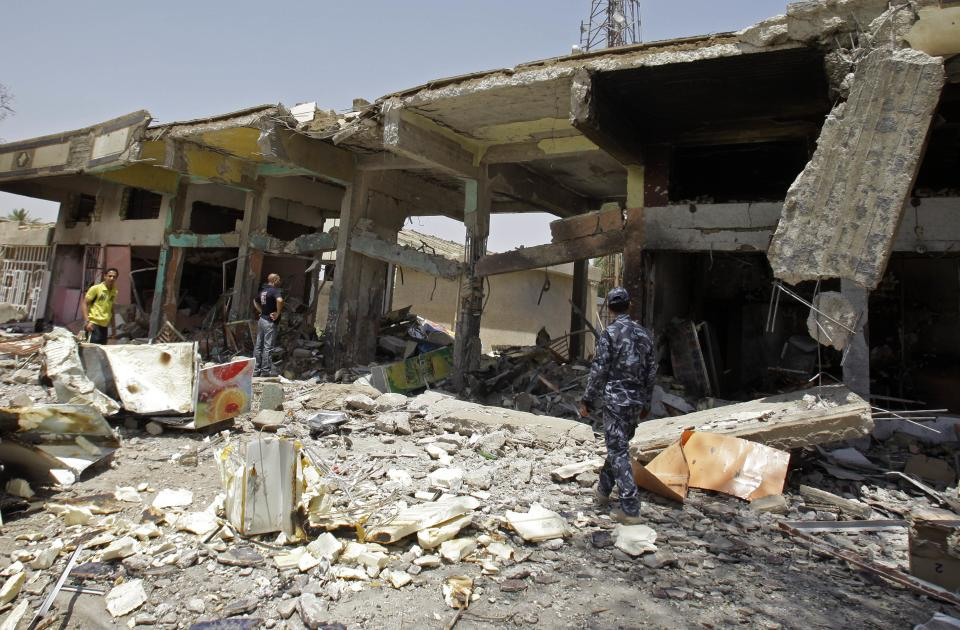 People inspect destroyed liquor stores in Baghdad, Iraq, Monday, May 23, 2011. Two bombs were planted near five liquor stores in the Zayouna area of eastern Baghdad, police said. (AP Photo/Khalid Mohammed)