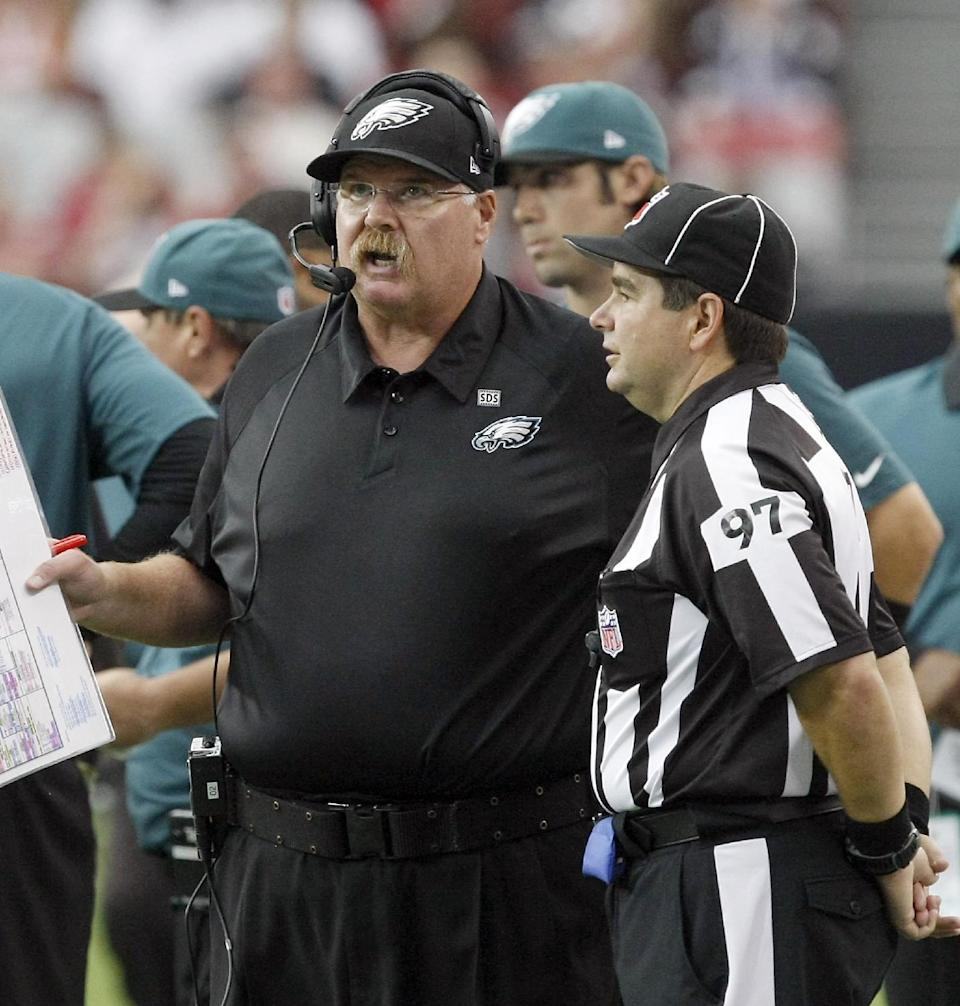 Philadelphia Eagles head coach Andy Reid, left, talks to NFL line judge George Shinkan in the fourth quarter during an NFL football game on Sunday, Sept. 23, 2012, in Glendale. (AP Photo/Rick Scuteri)
