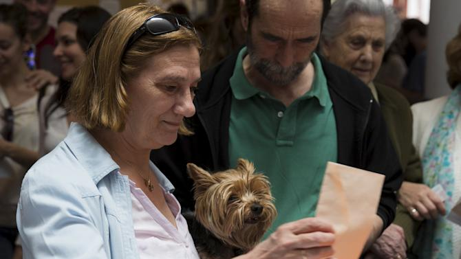 A voter holds onto her dog as she casts her ballot at a polling station during regional and municipal elections in Pozuelo de Alarcon, outside Madrid