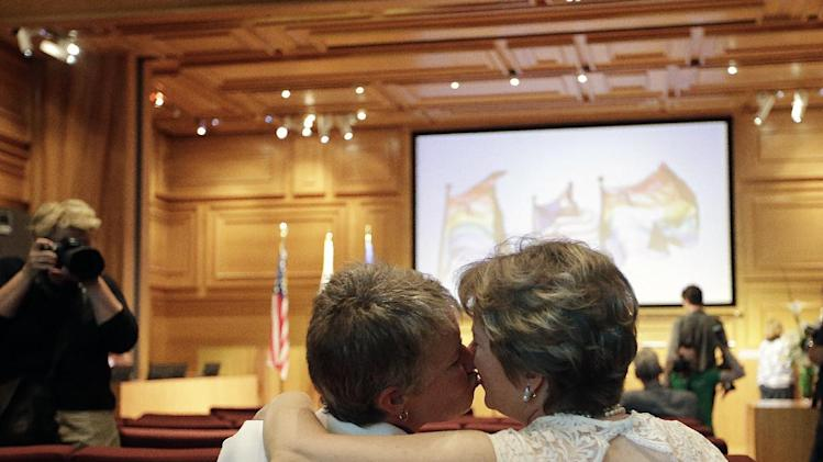 Faith Kassan, left, and her partner Jennifer Ehrman kiss before their wedding ceremony in West Hollywood, Calif., Monday, July 1, 2013. The city of West Hollywood is offering civil marriage ceremonies Monday for same-sex couples free of charge. (AP Photo/Jae C. Hong)