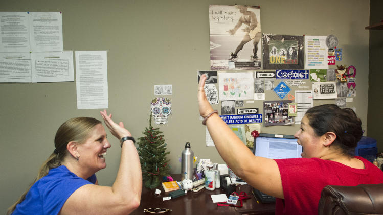 FILE - In this Dec. 23, 2013 file photo, Lisa Donlea, left, and Susan Roberts, a certified enrollment officer, celebrate after working on Donlea's federal health insurance exchange enrollment online for one hour and 47 minutes in Laguna Beach, Calif. The Obama administration says following a December surge, more than 1.1 million people have now enrolled for health insurance through the federal government's improved website. (AP Photo/The Orange County Register, Cindy Yamanaka, File)