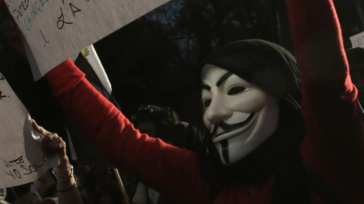 A protester wearing a Guy Fawkes mask participates with others civil organizations during a march against the radical reform of the country's energy market in Mexico City