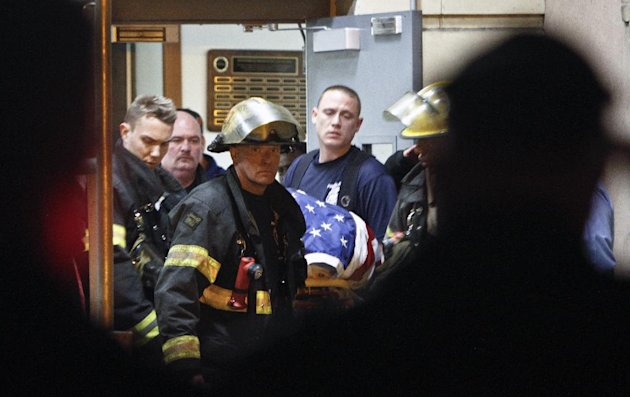 Fellow firefighters carry the body of fallen firefighter Capt. Michael Goodwin at Thomas Jefferson Hospital in Philadelphia, Saturday, April 6, 2013. The fire caused a partial roof collapse that killed Goodwin and injured a colleague who was trying to rescue him, officials said. (AP Photo/ Joseph Kaczmarek)