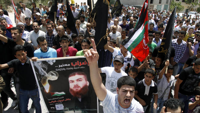 """Palestinians chant slogans during a rally in a West Bank village near Jenin, West Bank, supporting to Palestinian prisoner Bilal Diab, who is on a hunger strike to protest detention without trial, Friday, May 4, 2012. The Arabic on the poster reads, """"the strike will continue..till freedom, glory, and dignity."""" A Palestinian rights group said recently that half of about 5,000 Palestinian prisoners held by Israel are on a hunger strike, demanding an end to imprisonment without trial as well as better conditions. (AP Photo/Mohammed Ballas)"""