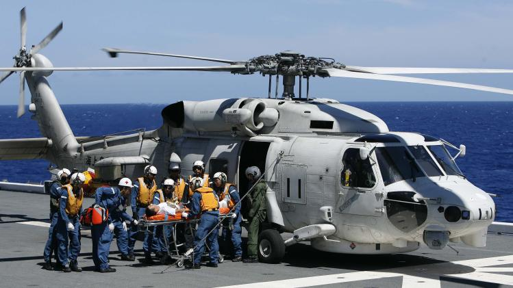 Members of the JMSDF unload a patient from a UH 60 Seahawk in a Humanitarian Assistance and Disaster Relief drill aboard the JMSDF ship JS ISE, south of Oahu during the RIMPAC in Honolulu