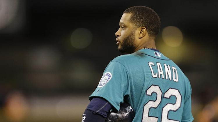 Seattle Mariners' Robinson Cano stands on the field after the umpire's call that had him safe at first was overturned by a challenge, resulting in a 2-1 loss for the Mariners to the Baltimore Orioles in the tenth inning of a baseball game, Friday, July 25, 2014, in Seattle. (AP Photo)