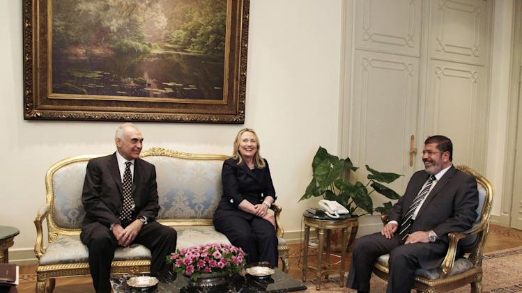Egyptian Foreign Minister Mohammed Kamel Amr, left, U. S. Secretary of State Hillary Clinton, center, and Egyptian President Mohammed Morsi, laugh during a photo opportunity at their meeting at the Presidential palace in Cairo, Egypt, Saturday, July 14, 2012. (AP Photo/Maya Alleruzzo)