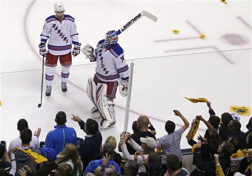 As Boston Bruins fans celebrate, New York Rangers goalie Henrik Lundqvist (30) and center Derick Brassard skate downice after losing 2-1 to the Bruins, eliminating the Rangers from the NHL playoffs in