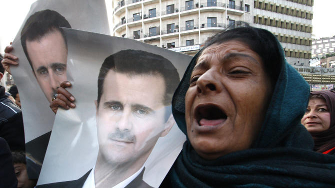 Pro-Syrian regime protesters, shout slogans and holds portrait of Syrian President Bashar Assad during a demonstration to show their solidarity for their president, in Damascus, Syria, on Wednesday Jan. 25, 2102. Government forces clashed with army defectors and stormed rebellious districts in central Syria on Wednesday, firing mortars and deploying snipers in violence that killed at least seven people, including a mother and her 5-year-old child, activists said. (AP Photo/Muzaffar Salman)