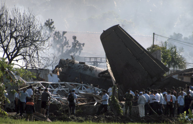 Indonesian military personnel investigate the site where an Indonesian air force plane crashed, in Jakarta, Indonesia, Thursday, June 21, 2012. The Fokker F-27 turboprop plane crashed into homes during a routine training flight in the capital Thursday, killing at least six people. (AP Photo/Teguh Windharto)