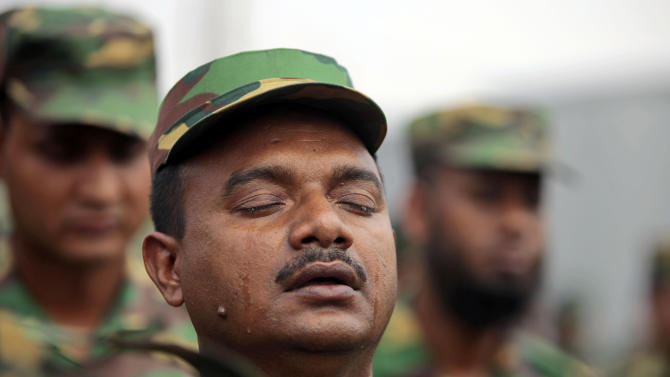 Tears roll down the cheeks of a Bangladesh army soldier as he offers prayers for the souls of the 1,127 people who died in the garment building structure collapse last month, in Savar, near Bangladesh, Tuesday, May 14, 2013. The Islamic prayer service was held a day after the army ended the nearly three-week, painstaking search for bodies among the rubble of the worst tragedy in the history of the global garment industry and turned control of the site over to the civilian government for cleanup. (AP Photo/A.M. Ahad)