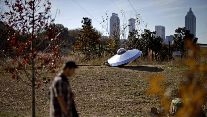 """In this Nov. 20, 2012 photo, Cash Barnes' public art project """"Take Me To Your Leader,"""" is seen against the downtown skyline along the Atlanta BeltLine in Atlanta. Since an Atlanta nonprofit opened a 2.25-mile-long paved trail east of downtown last month, it has attracted a steady stream of joggers, dog-walkers and cyclists to take in spectacular views of the skyline as well as a slice of established neighborhoods that were once only seen by riding a freight train. The Eastside Trail is the latest and most visible phase of the Atlanta BeltLine, an ambitious $2.8 billion plan to transform a 22-mile railroad corridor that encircles Atlanta into a network of parks, trails, public art, affordable homes and ultimately streetcars. (AP Photo/David Goldman)"""