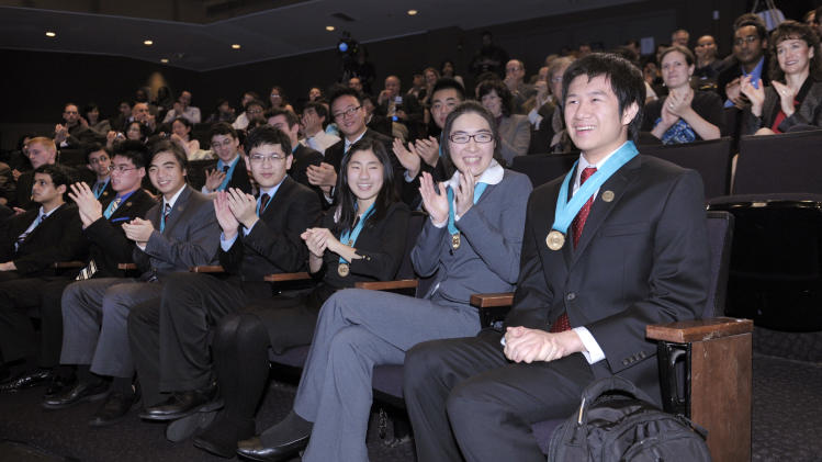 Kensen Shi, a senior at A&M Consolidated High School in College Station, Texas, right, is applauded at George Washington University in Washington, Tuesday, Dec. 4, 2012, after winning the $100,000 Grand Prize in the Individual category of the Siemens Competition in Math, Science & Technology National Finals. (AP Photo/Susan Walsh)