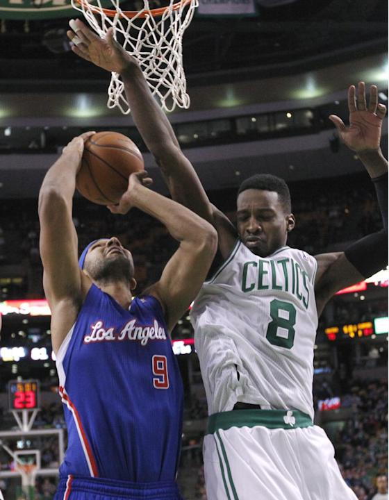 Los Angeles Clippers forward Jared Dudley (9) tries to go up for a shot against the defense of Boston Celtics guard Jeff Green (8) in the second half of an NBA basketball game in Boston, Wednesday, De
