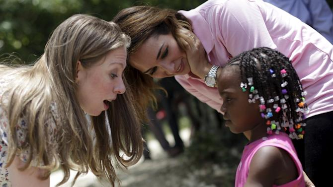 Clinton Foundation Vice Chair Chelsea Clinton receives a gift from a Haitian girl during a visit to Chakipi Distribution Enterprise in Poulie