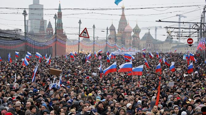 People carry Russian national flags during a march in memory of opposition leader Boris Nemtsov who was gunned down on Friday, Feb. 27, near the Kremlin, with The Kremlin Wall and St. Basil Cathedral in the background,  in Moscow, Russia, Sunday, March 1, 2015. Thousands converged Sunday in central Moscow to mourn veteran liberal politician Boris Nemtsov, whose killing on the streets of the capital has shaken Russia's beleaguered opposition. (AP Photo/Dmitry Lovetsky)