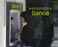 A woman uses a Bankia bank automated teller machine (ATM) in Madrid