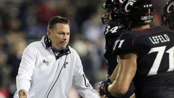 FILE - In this Oct. 13, 2012, file photo, Cincinnati head coach Butch Jones, left, slaps hands with his players as they run off the field after scoring a touchdown in the second half of an NCAA college football game against Fordham in Cincinnati. The bowl-bound Bearcats wait to hear from coach Jones about whether he'll stay or head off to either Purdue or Colorado. (AP Photo/Al Behrman, File)