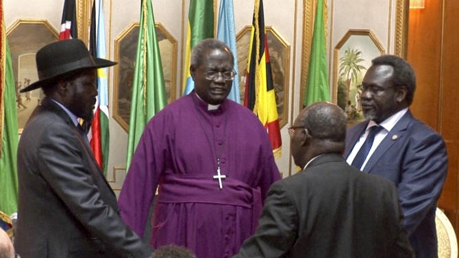 In this Friday, May 9, 2014 image made from video, South Sudan's President Salva Kiir, left, and rebel leader Riek Machar, right, shake hands and pray before signing an agreement of the cease-fire of the conflict in South Sudan in Addis Ababa, Ethiopia. The South Sudan's president has reached a cease-fire agreement with the rebel leader, an African regional bloc said Friday, after a vicious cycle of revenge killings drew international alarm. (AP Photo/AP Video)