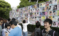 FILE - In this June 6, 2012 file photo, fans of Japans all-girl pop idol group AKB48 take photos of the members&#39; election posters outside the venue of the annual AKB48 popularity poll in Tokyo. More than 60 girls and young women, split into four teams, make up what is arguably Japan&#39;s most popular pop group. It performs almost every day, has spawned affiliate groups across the country and has recently given rise to sister mega-groups in China and Indonesia. (AP Photo/Shizuo Kambayashi, File)