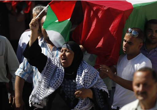 A Palestinian woman shouts as others carry a flag-covered coffin containing the remains of a Palestinian militant following a ceremony in Ramallah