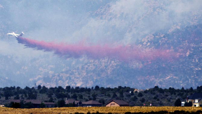 A tanker make a retardant drop while fighting the Doce Fire near Prescott, Ariz., Wednesday, June 19, 2013. The wildfire that has burned nearly 8 square miles just west of Prescott had moved into people's backyards and has forced the evacuation of 460 homes. (AP Photo/The Arizona Republic, Pat Shannahan)  MARICOPA COUNTY OUT; MAGS OUT; NO SALES