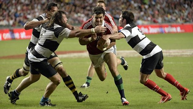 Mike Phillips of the Lions (C) runs with the ball as Dimitri Yachvili (R) and Martin Castrogiovanni (front L) of the Barbarians try to defend during the British and Irish Lions friendly rugby match against the Barbarians at Hong Kong Stadium (AFP)