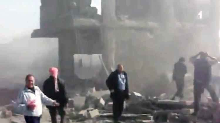 This image taken from video obtained from Shaam News Network, which has been authenticated based on its contents and an Associated Press journalist who saw a plane bomb an area around the Syrian-Turkish border town of Ras al-Ayn, shows Syrians inspecting the damage and looking for victims moments after an airstrike by Syrian warplanes in Ras al-Ayn, Syria, Monday, Nov. 12, 2012. (AP Photo/Shaam News Network via AP video)