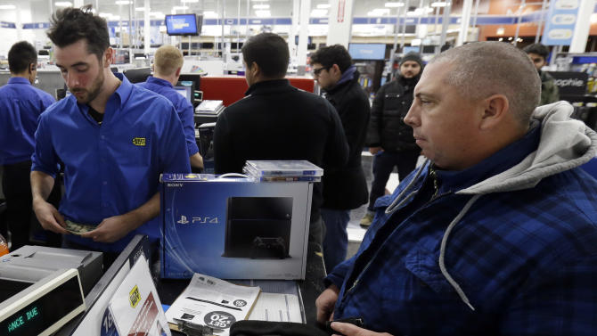 Dean Gentry from Chicago, right, purchases his Sony Playstation 4 from Gino Boccardi at Lincoln Park BestBuy store in Chicago on Friday, Nov. 15, 2013. The PlayStation 4, came out Friday. The Xbox One, goes on sale next week.(AP Photo/Nam Y. Huh)