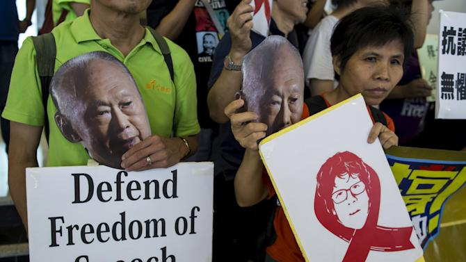 Protesters hold up pictures of Singapore's first Prime Minister Lee during a protest to demand the release of Singaporean teenager Yee outside the Singapore Consulate in Hong Kong
