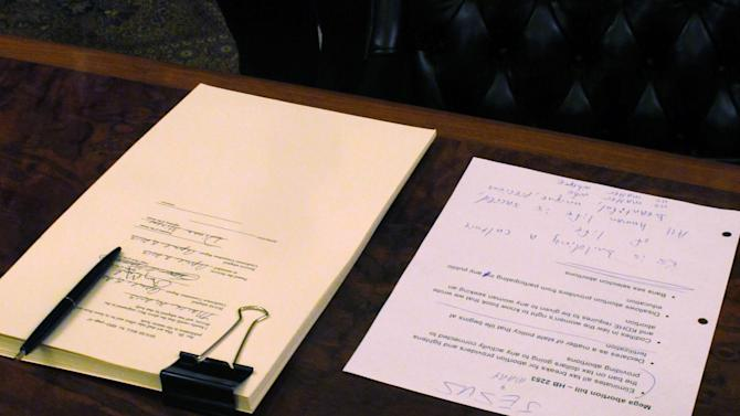 """FILE - Anti-abortion legislation, left, sits on a desk in Kansas Gov. Sam Brownback's ceremonial office as he prepares to sign it at the Statehouse in Topeka, Kan. on Friday, April 19, 2013. At right is a page of Brownback's notes about the measure with """"JESUS + MARY"""" written at the top. Further down the page are typewritten notes spelling out Brownback's belief that the bill would create """"a culture of life."""" Since the Republican electoral gains of 2010, GOP-dominated state legislatures have passed more than 160 restrictive abortion measures - more than in the seven previous years combined, according to a tally by the Guttmacher Institute. (AP Photo/John Hanna)"""