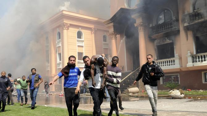 An injured security official is carried from a police officers club in the upscale neighborhood of Zamalek, after protesters set fires following a court verdict in Cairo, Egypt, Saturday, March 9, 2013. Fans of Cairo's Al-Ahly club have stormed Egypt's soccer federation headquarters and a nearby police club, and set them ablaze after a court acquitted seven of nine police official on trial for their alleged part in deadly stadium melee. (AP Photo/Mohammed Asad )