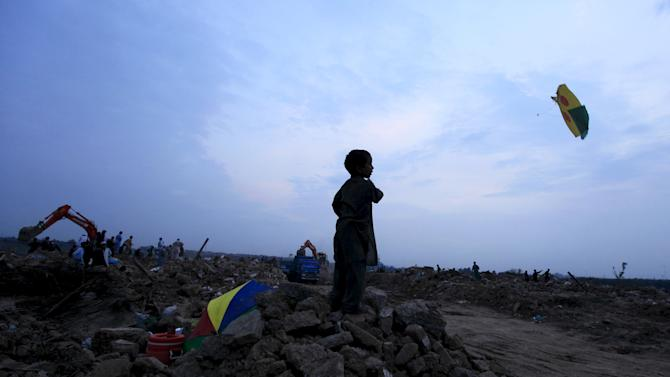 A boy flies a kite at debris of family's house as excavator destroys neighborhood at slum on the outskirts of Islamabad