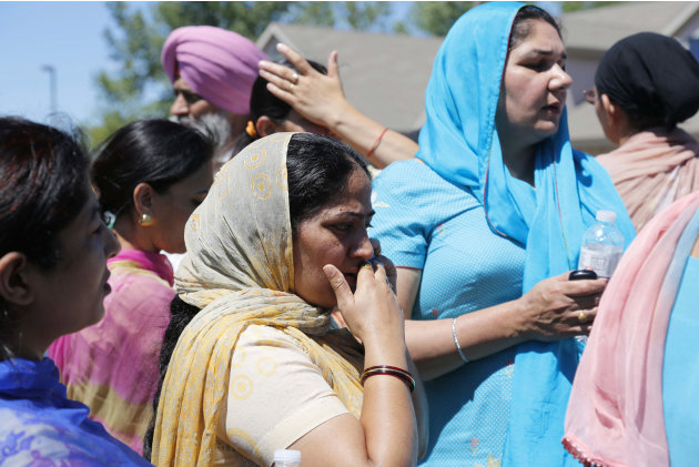 Bystanders stand outside the scene of a shooting inside The Sikh Temple in Oak Creek, Wis, Sunday, Aug. 5, 2012. Police in Wisconsin say at least seven people are dead at a Sikh temple near Milwaukee,