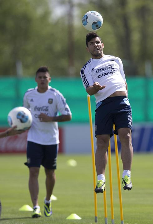 Argentina's Sergio Aguero, right, heads the ball during a team training session ahead a Brazil 2014 World Cup qualifying soccer match against Peru in Buenos Aires, Argentina, Tuesday, Oct. 8, 2013