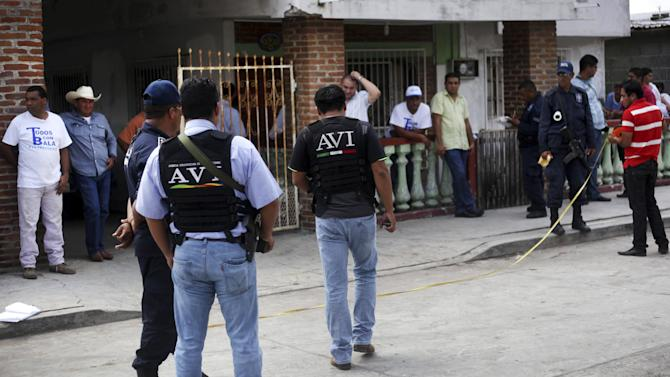 In this Monday, July 1, 2013, state police and forensic experts stand outside the home of mayoral candidate Carlos Triana Garcia after unknown gunmen opened fire on his home in Tlalixcoyan, Mexico. With only days to go in the campaign for Sunday's elections in 14 states, at least eight local politicians or their family members have been killed. Others have reported being kidnapped or shot at. Triana Garcia of the conservative National Action Party woke up at 4 a.m. Monday to a spray of gunfire on his house in the Gulf coast state of Veracruz. No one was injured in that incident, though 11 bullet casings were found. (AP Photo/Felix Marquez)
